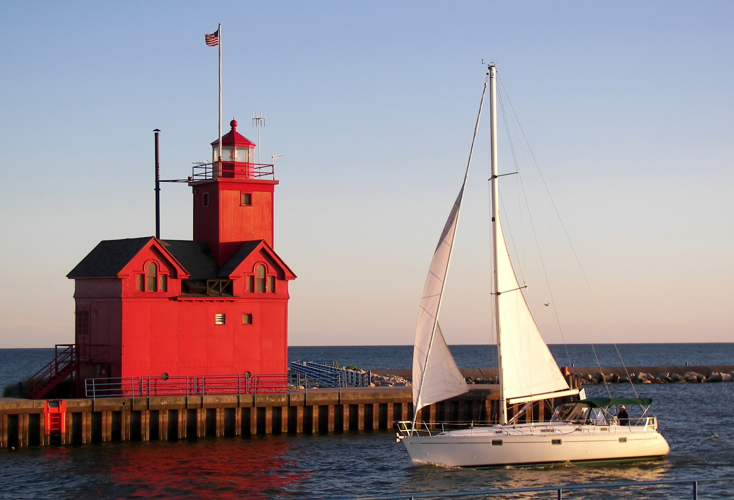 big red light house with sail boat on lake michigan