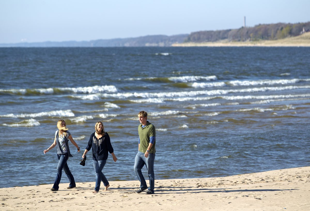 a group of three students walking on the beach