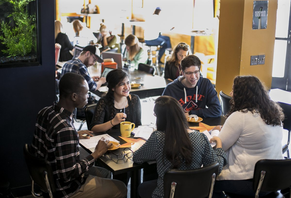 group of students sitting around a table in a coffee shop talking