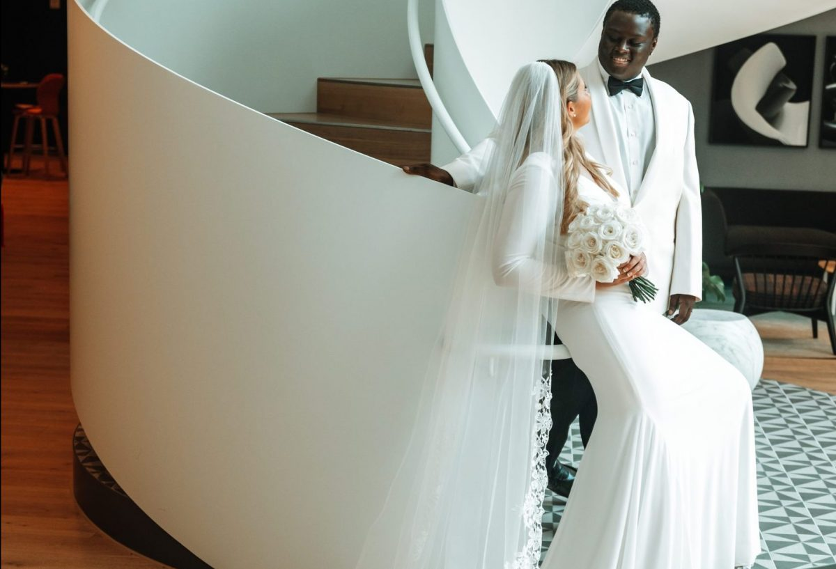 couple leaning on lobby staircase annie lane bridal garments